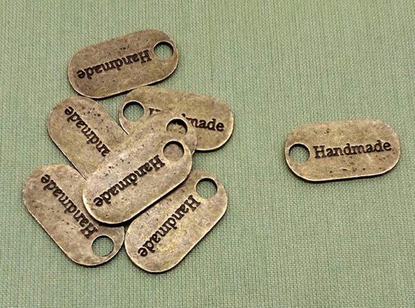 """Chapa ovalada """"Hand made"""". Bronce. 23x13 mm"""